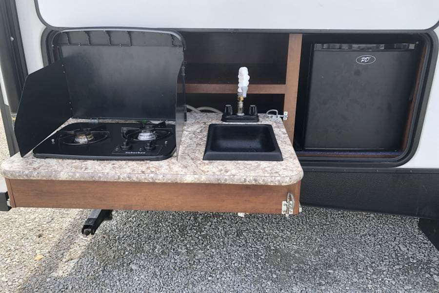 Outdoor kitchen with mini-fridge, two burner propane stove, and sink.