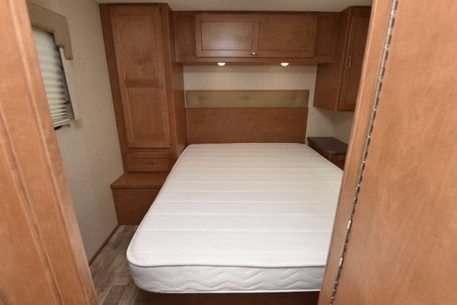 The master bedroom with a queen size bed, side and front overhead storage cabinets, and a wardrobe.  We provide clean, lovely linens, pillows, and blankets. We only supply items we would use in our own home!