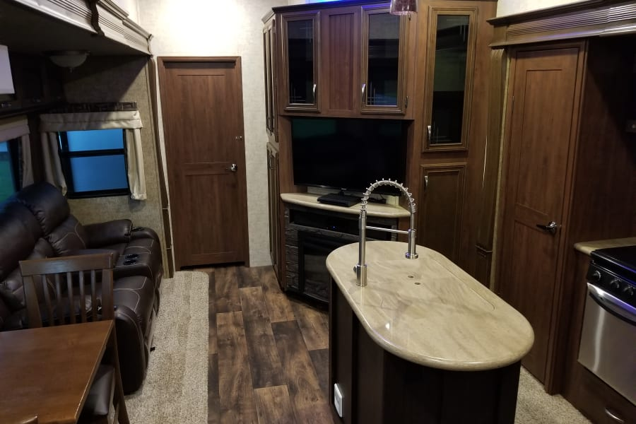 Main cabin area with 2 reclining leather chairs that also massage and heat up. Tv, dining room set and kitchen area with granite counter tops.