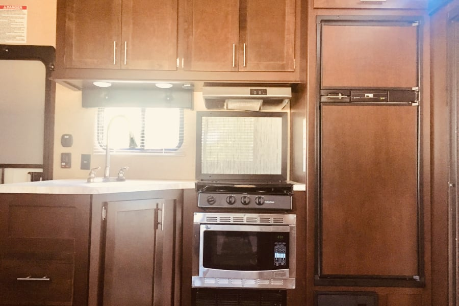 Kitchen area with plenty of cabinet space includes refrigerator, sink, microwave/oven combo and 3 burner gas stove top.
