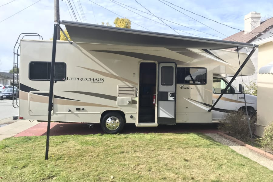 Entry door with screen. Awning can be staked to the ground or mounted on the side of the RV.