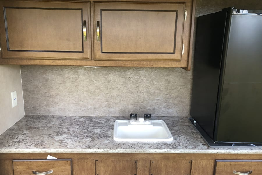 Outdoor kitchen complete with storage, sink, stove/ grill and mini fridge for lots of fun outdoors!