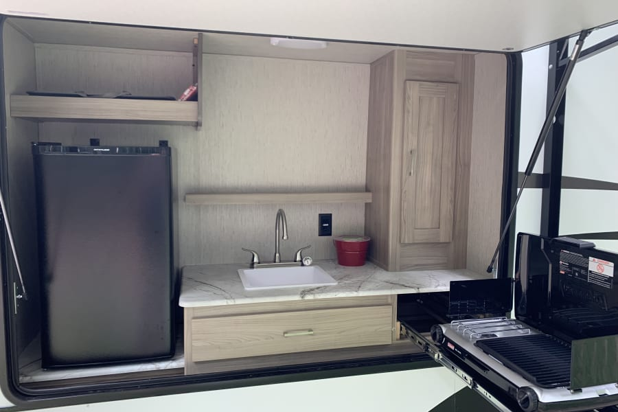 Outdoor kitchen with mini-fridge, sink, and gas grill.