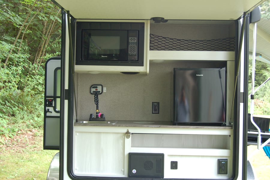 Nice kitchen with sink, refrigerator, and microwave.