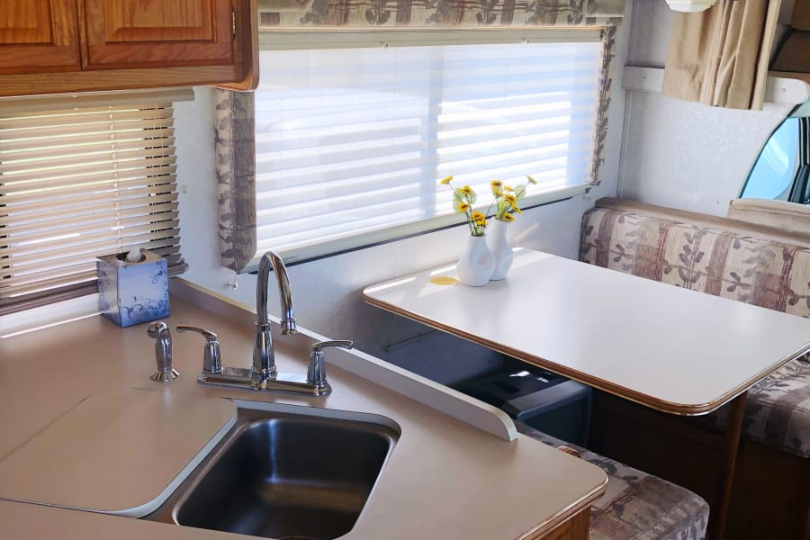 Double sided stainless steal sink with a cutting board. Dinette makes into a bed for two children or one adult.  Faucet set is new.