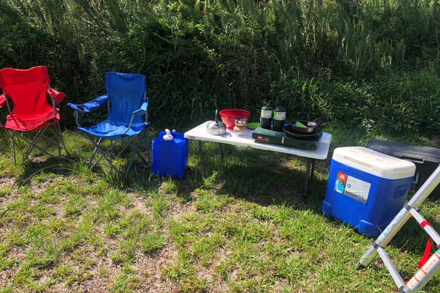 2 Chairs, Table, Cooler, 2 burner  Cook stove, propane, bed linens, towels, cookware, 5 gallons of water, Cooking supplies, coffee maker
