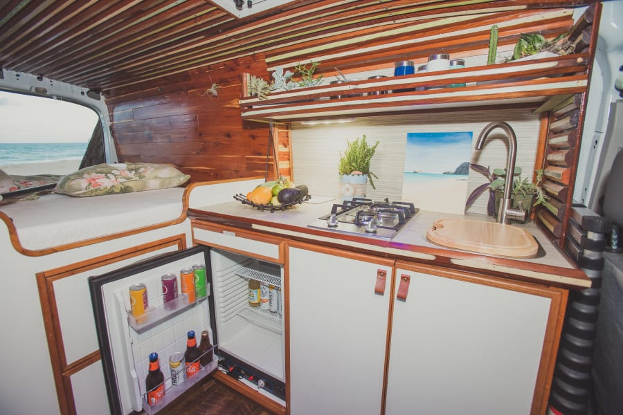 Full kitchen with large sink, two burner propane stove, mini-fridge, and all the cooking utensils you need to make you feel at home