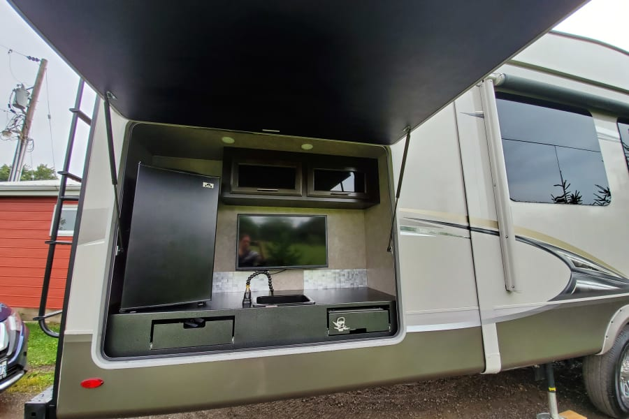 Outdoor kitchen equipped with: bar fridge, storage, sink, TV and grill