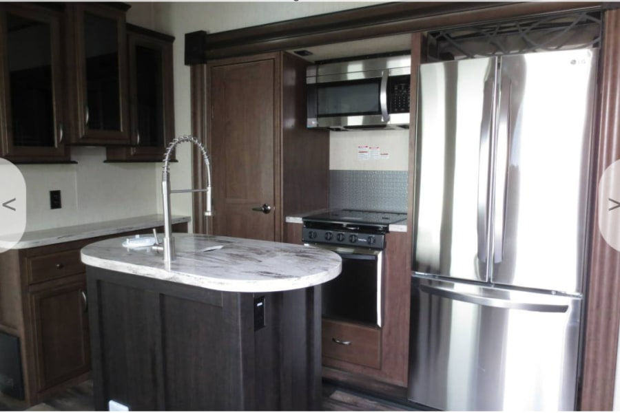 Spacious kitchen with a pantry, cabinets, microwave, stove top and oven.