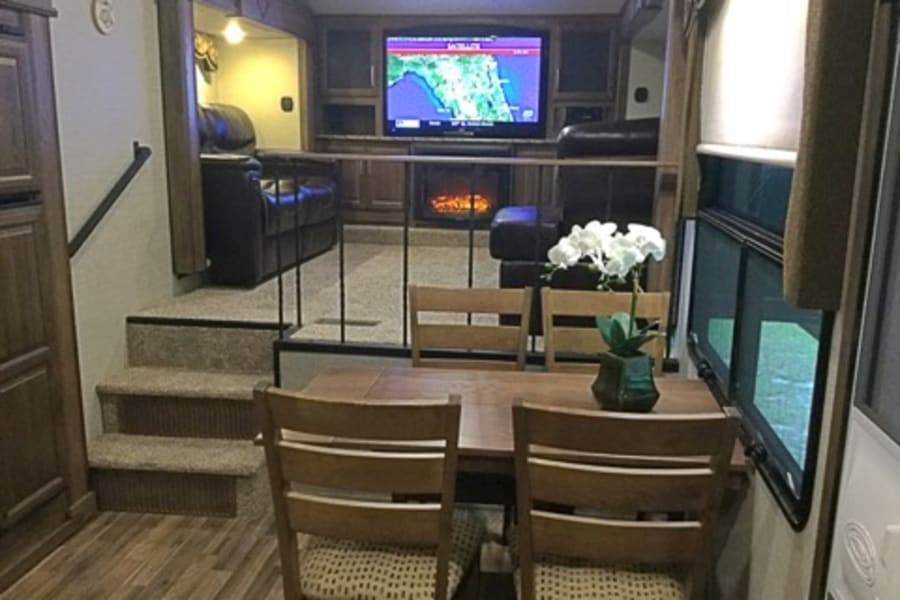 A look into the living room from the kitchen.  The living room is in the upper level of the RV and offers a safety rail to keep the young ones and your canine family members safe while the open floor plan between the living room and kitchen is great for entertaining and family gatherings.  The pull out sofa bed adds additional sleeping space and the extra large couch can be used as a bed as well. We supply linens and pillows for both.