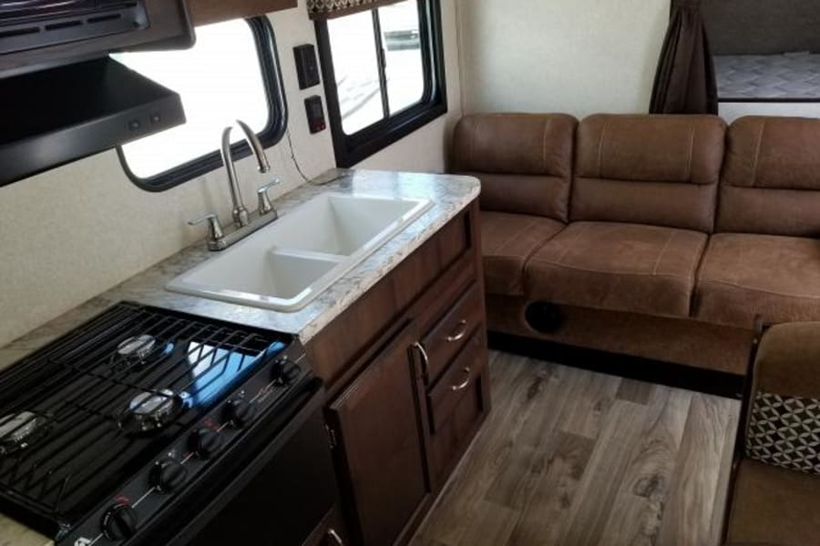 Ample kitchen with refrigerator, freezer, oven, stove, sink and cupboards beside a comfortable couch.