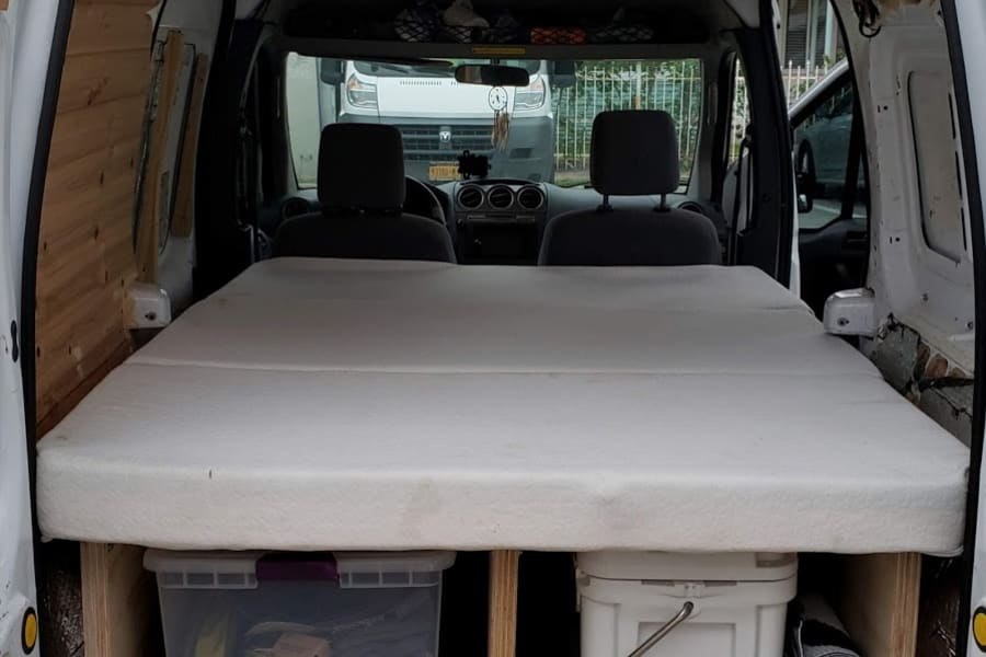 Bed has been raised 14 inches to accommodate storage below. Comes with a mattress that folds in 3.
