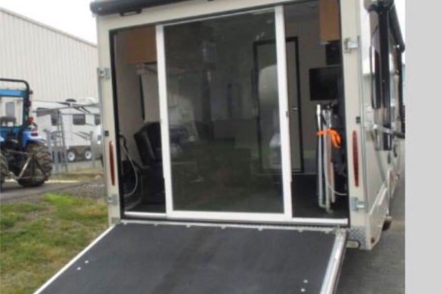 ramp into the toy hauler area, this ramp easily converts to a deck. The exterior light, awning and sliding lexan doors make it an extra space for the adults to hang out and not disturb the sleeping kids