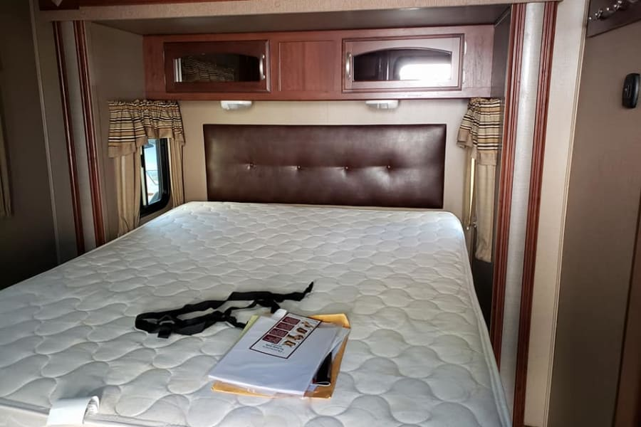 Master bedroom with a regular mattress and not a camper mattress. Additional storage is available under the bed.