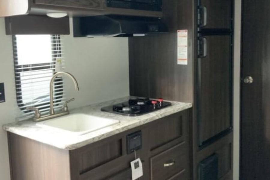 Kitchen area- sink, 2 burner stove, microwave, refrigerator and freezer