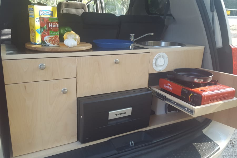 Your galley kitchen, fully equipped with utensils and cooking equipment for two.  Single burner propane/butane stove, 10 gallon hand pump fresh water system with 5 gallon grey water tank.  Dometic 12 volt drawer style refrigerator with a 31 quart capacity has plenty of space for your essentials!