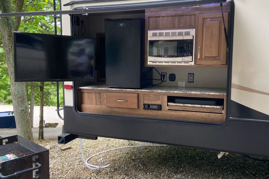 Outdoor kitchen with cooktop, TV/radio, microwave, refrigerator and storage