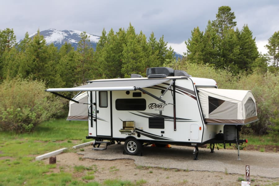 Grill is covered with a power awning and lit with LED lighting (grill attaches to camper and is available to rent in add-ons)