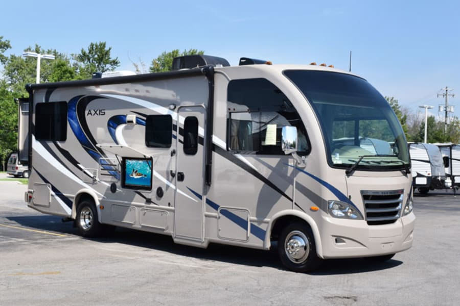 Exterior image of Coach. Exterior television and overhead awning. Several exterior doors for extra storage.