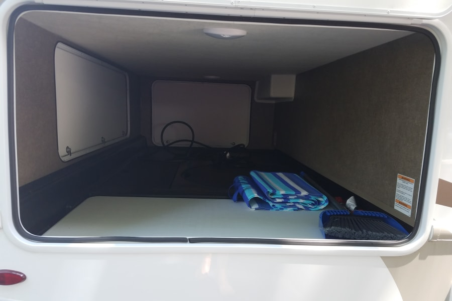 Huge outside storage the width of coach with 3 access doors and notice the 4 ft white table