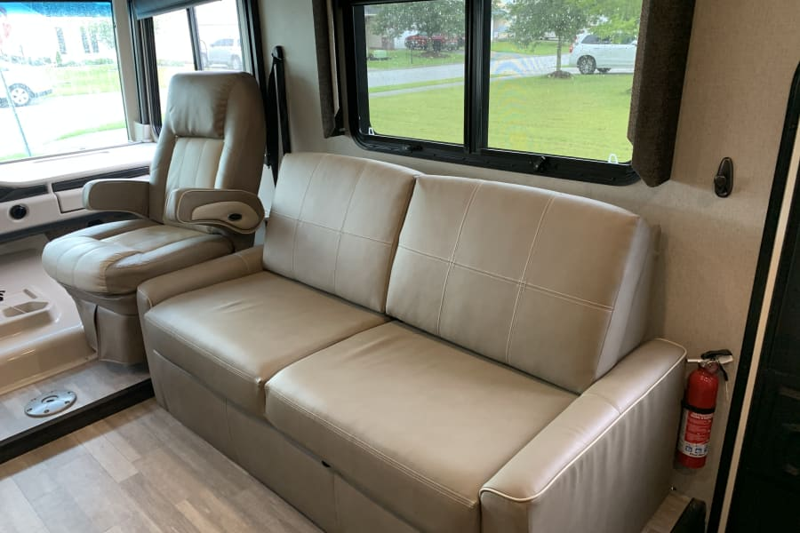 Love seat sofa and captains chair for lounging or watching TV.