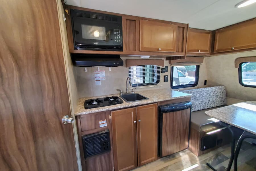 Kitchen with 2 burner stove, hood/microwave, sink, and fridge.