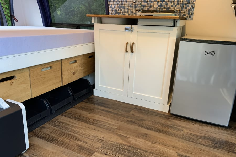 Small kitchen with sink, tqo burner stove, and small fridge.Underbed crates make for easy storage of essentials.