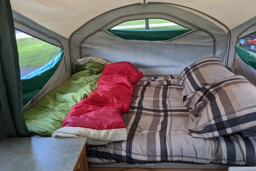 Queen size bed in front with extra sleeping bags