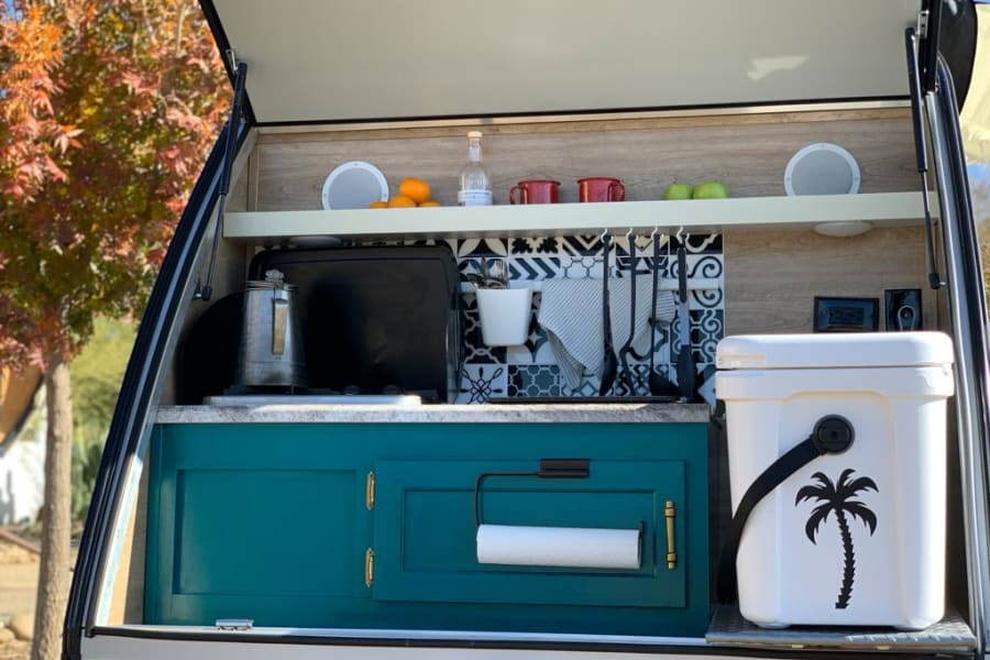 We got all the basics covered: Cooler, sink, 2 burners, percolator, griddle, pot, mugs, glasses, cutting board, utensils, bowls, and plates for two.