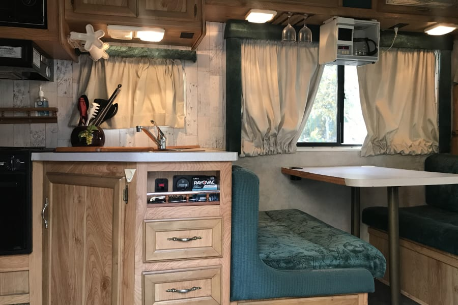 This shows the entrance of the RV, including the generator and water pump controls, the kitchen sink and the dining table/sleeping area.