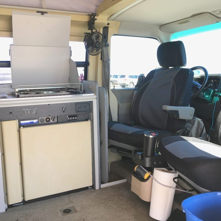 Interior with seats rotates, showing fridge and stove.