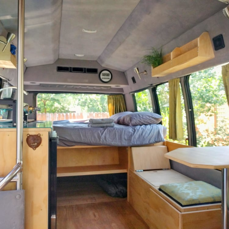 The view from the swiveled passenger seat shows the overall layout.  Bed, storage, bench, booth, and kitchen counter.