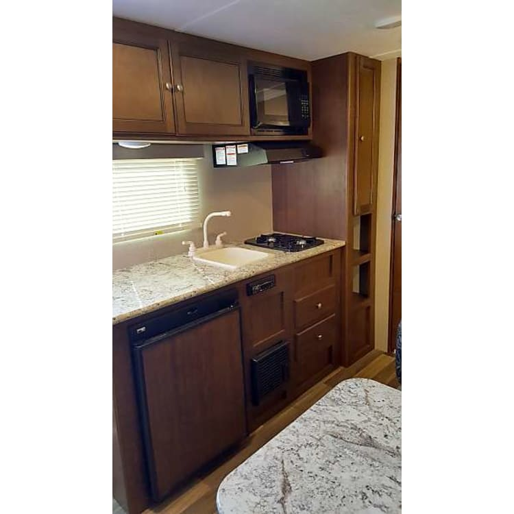 The kitchen has plenty of prep space with a dual top stove, microwave, and a sink with hot and cold water.