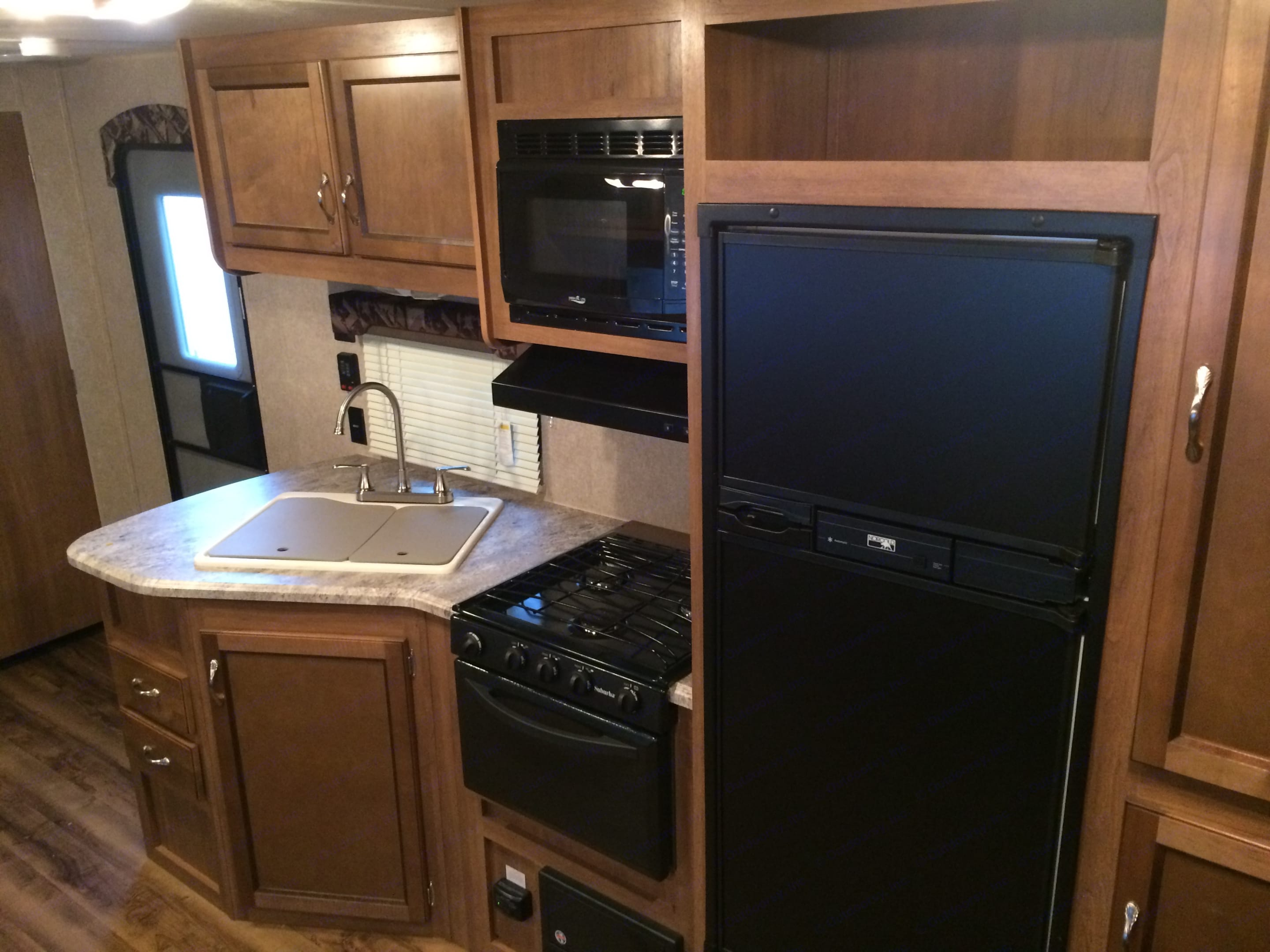 Kitchen with double sink, fridge/freezer, microwave, stove, and oven. Coachmen Catalina SBX 2016