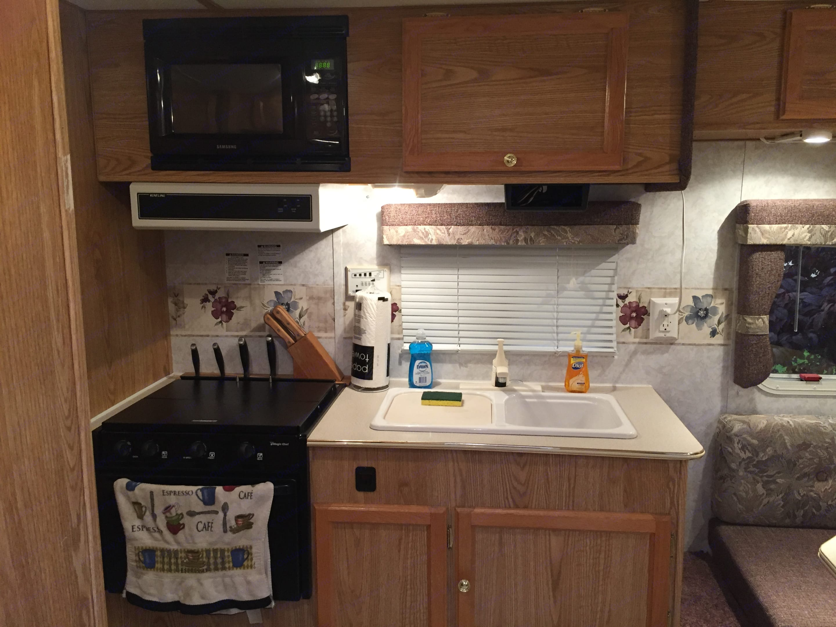 Kitchen with microwave, 3 burner stove, oven, and double bowl sink. Thor Motor Coach Tahoe 2004