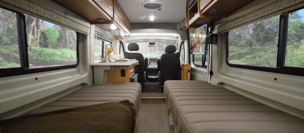 """The cabin is open & airy with lots of windows and two twin lounges with reclying headrests for napping in front of the 24"""" HDTV entertainment system.. Winnebago Travato 2018"""