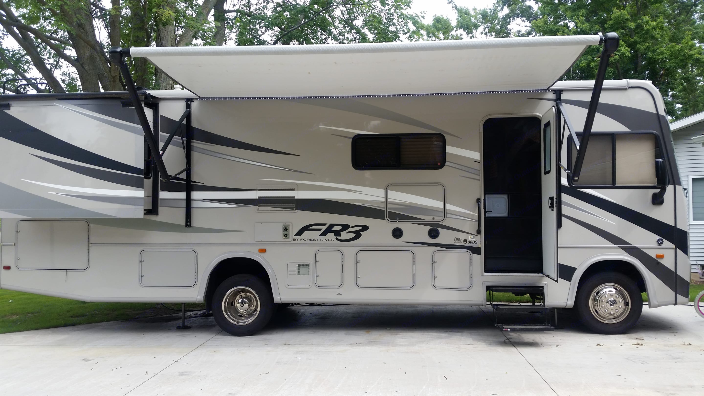 Door to enter RV. Awning where a carpet sits while camping with 4 bag chairs.. Forest River Fr3 2017