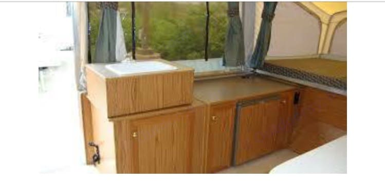 Taken prior to improvements. Cabinets were stained and linoleum has been replaced with wood flooring.. Starcraft Camping Trailers 2003