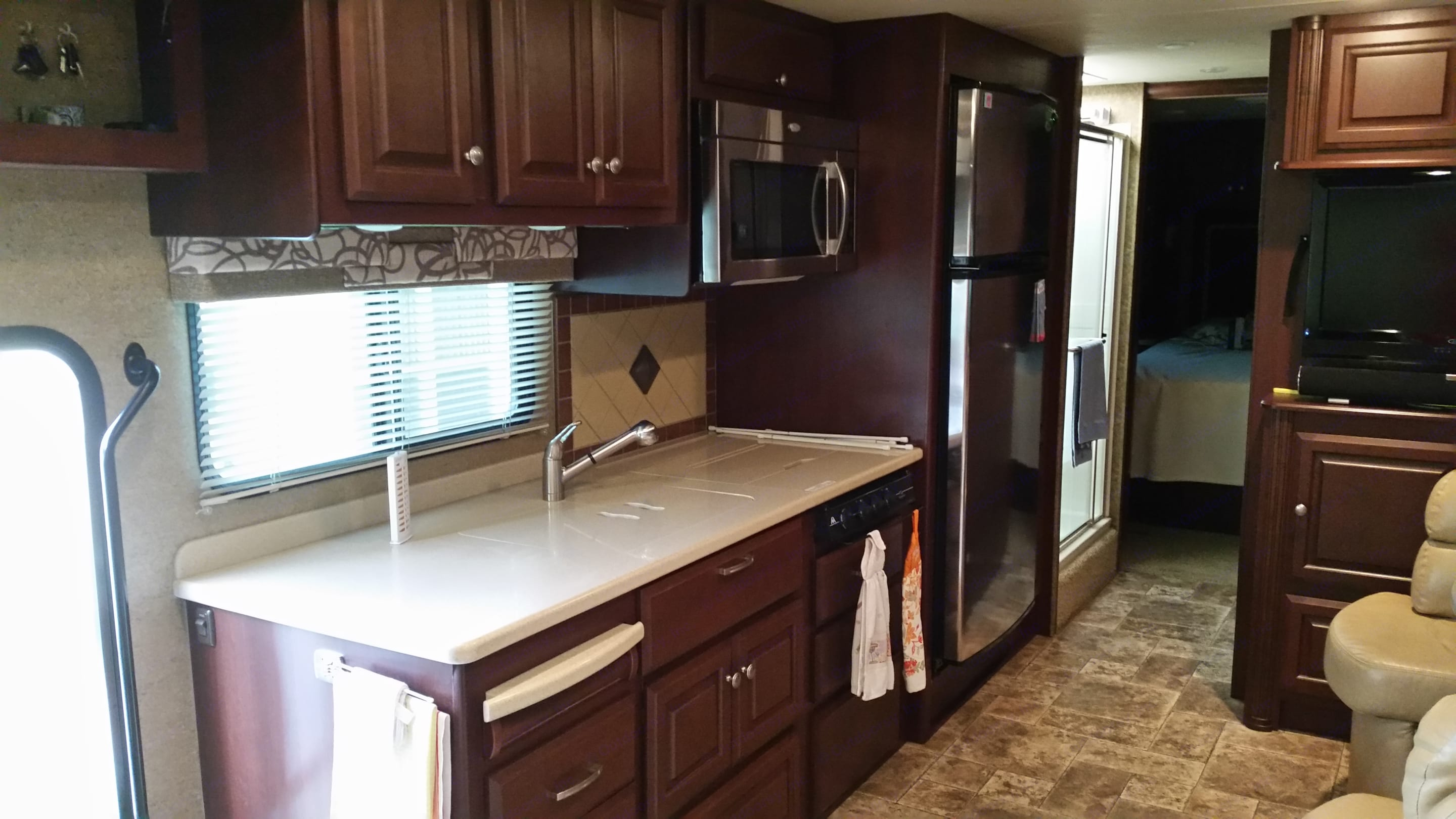 Kitchen with Solid surface counters, Microwave/Convection & 18 Cubic foot Residential Refrigerator with icemaker. Thor Motor Coach Palazzo 2013
