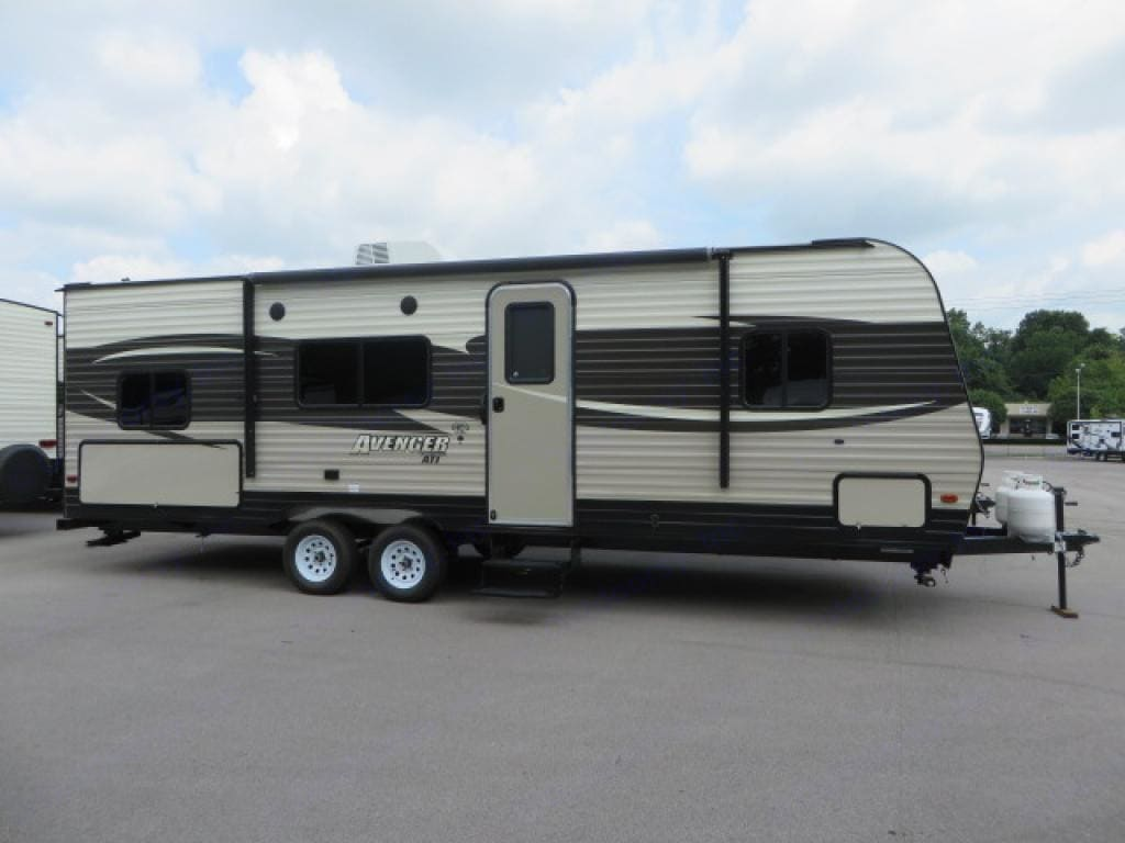 Outside view of travel trailer. Extra storage, fold out stairs, electric owning, and outdoor kitchen area. . Prime Time Avenger 2018