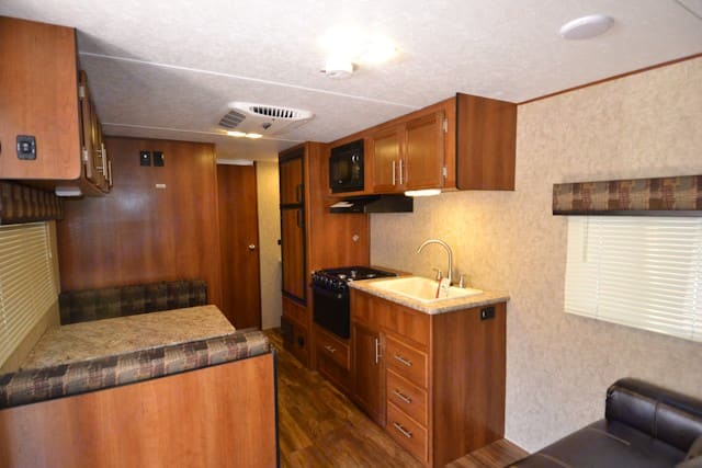 Kitchen area with three burner stove, oven, and microwave. Table that seats four and folds down into a bed. . Prime Time Avenger 2018