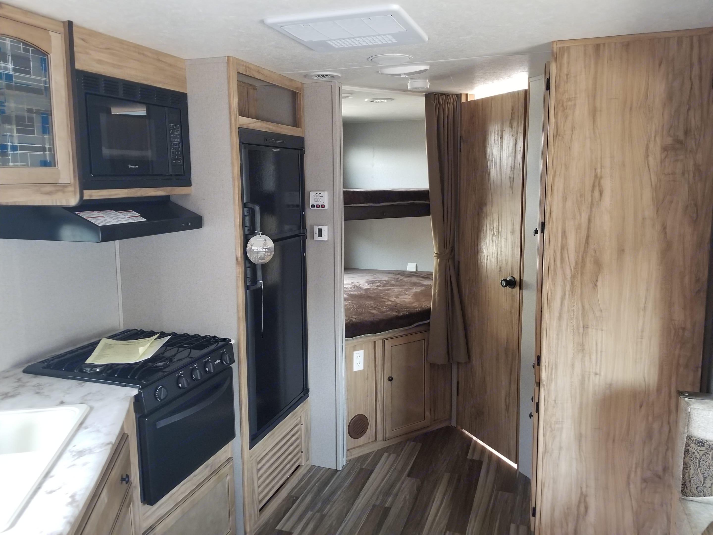 Living space showing the 2 queen bunks and bathroom door. Coachmen Freedom Express 2018