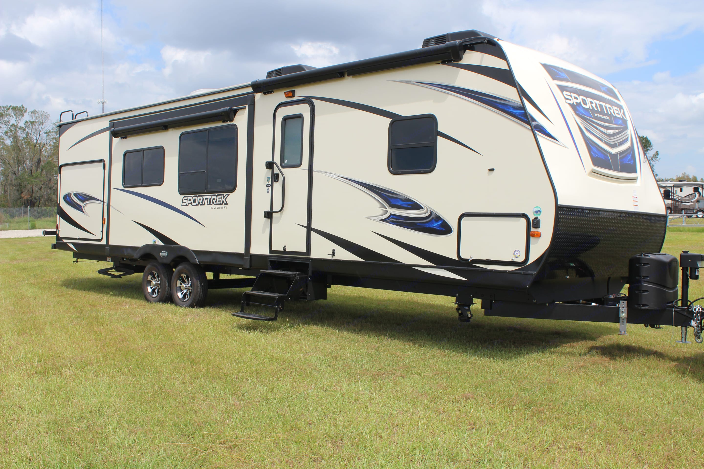 Exterior view of RV, shows entrance way as well as one of the slides and the two awnings.. Venture Rv Sporttrek 2018