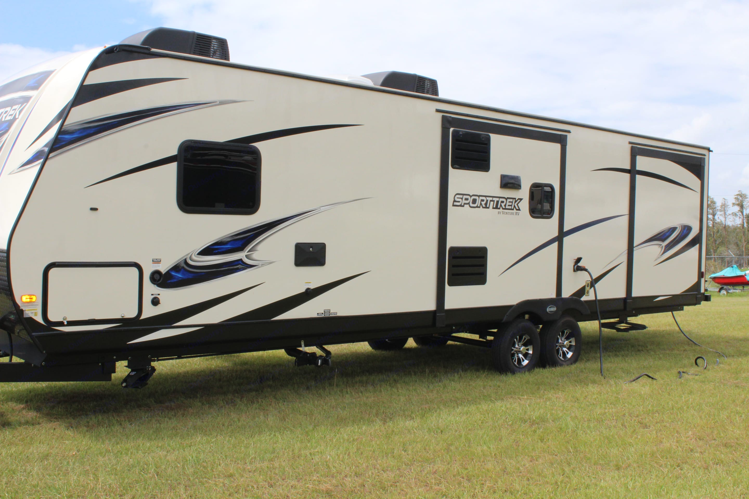 Other exterior view of the RV, which shows the other two slides as well as the front through storage area. . Venture Rv Sporttrek 2018