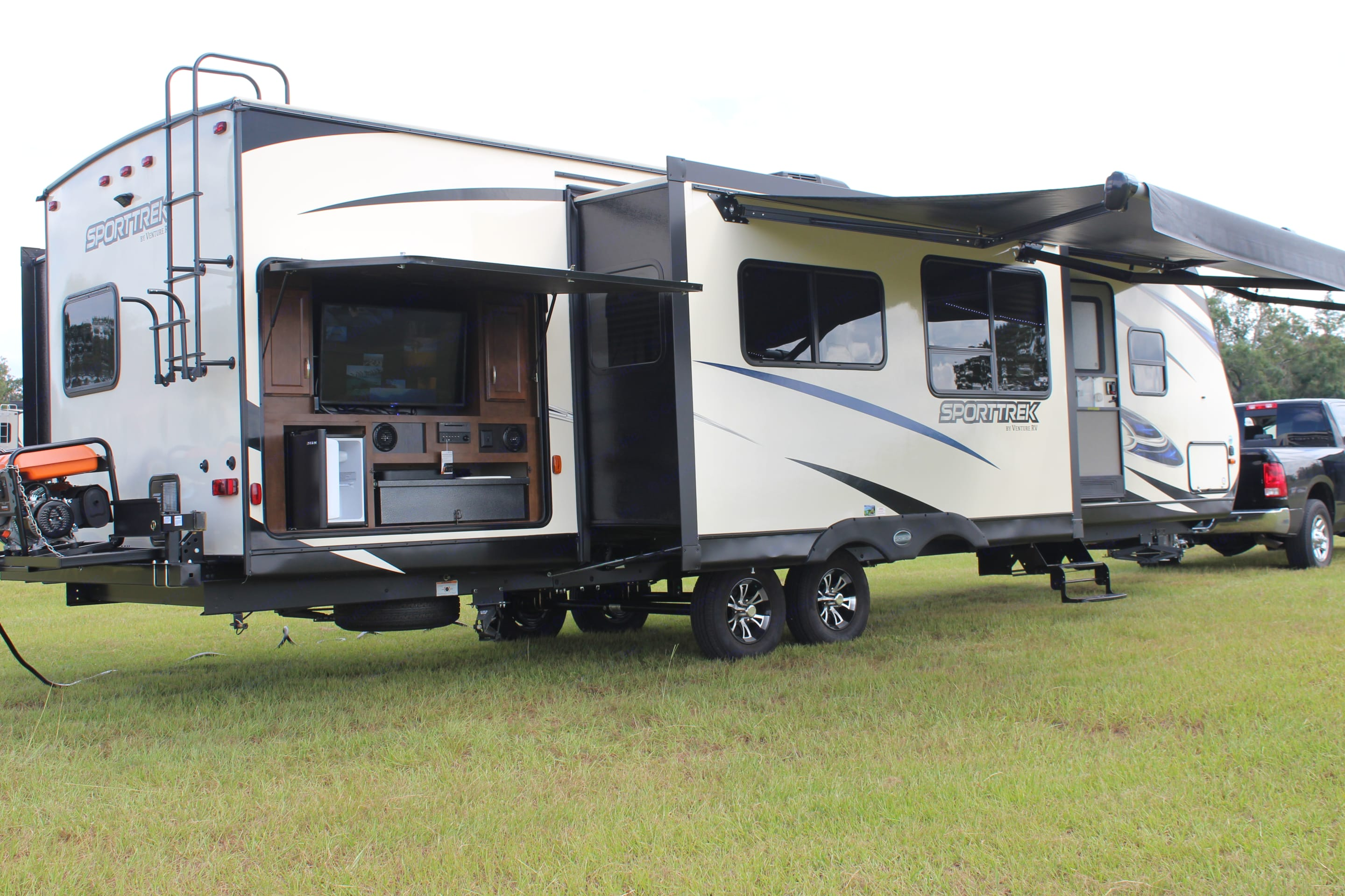 Exterior view which shoes the outdoor kitchen/entertainment area. The outdoor kitchen area is equipped with a large TV, two burner stove, sink, refrigerator, and storage.. Venture Rv Sporttrek 2018