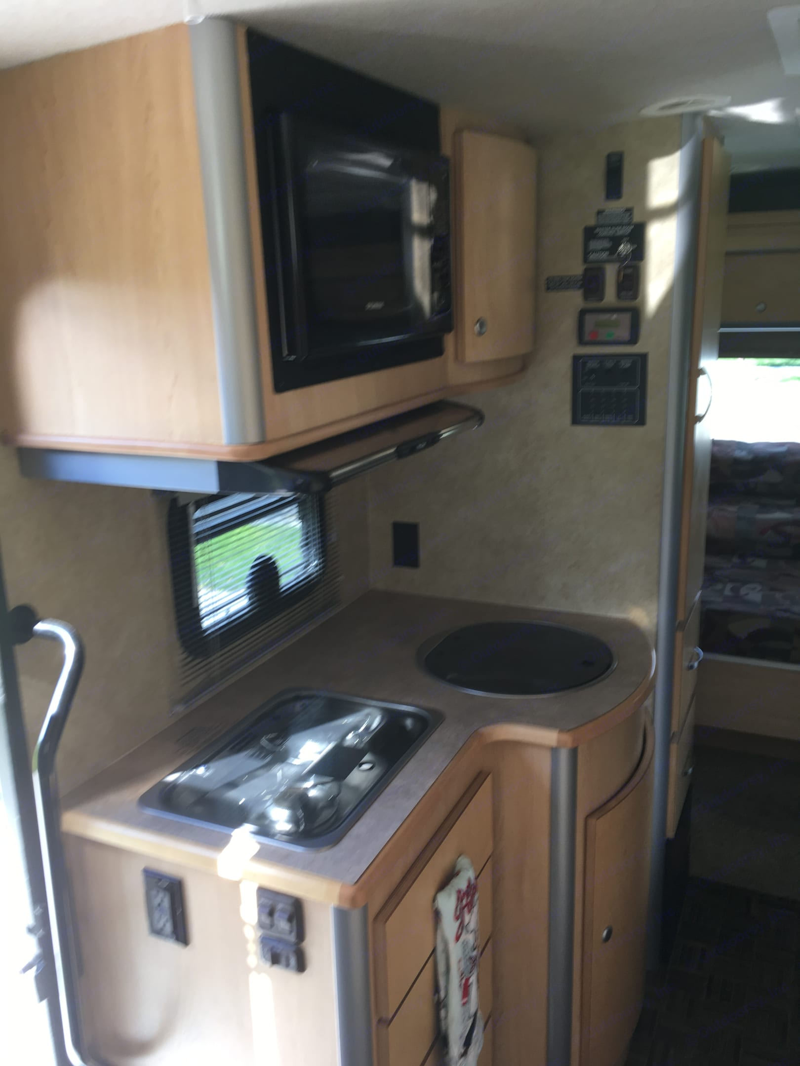 Kitchen with 2 gas burners, sink, microwave and overhead hood. Itasca Navion 2008