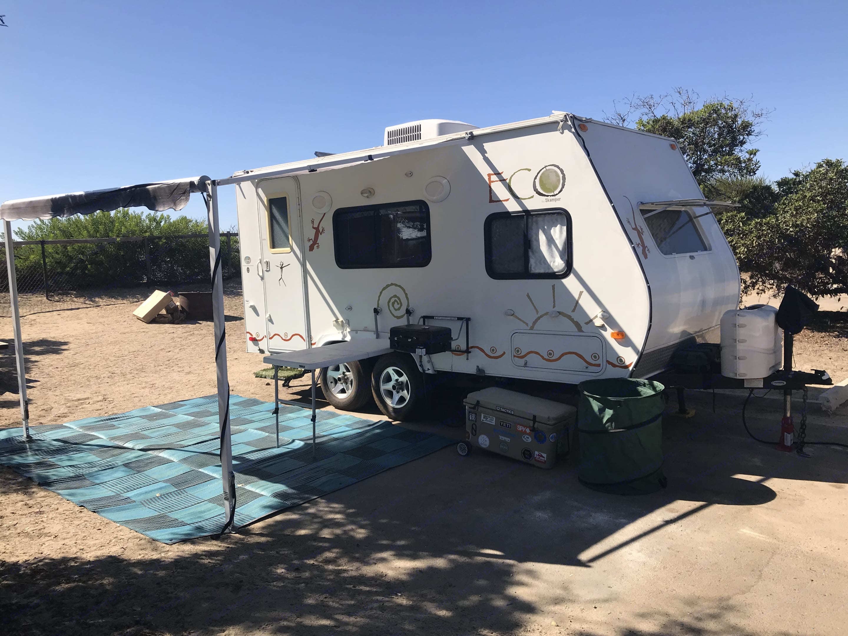 The trailer has Thule attachable table and BBQ grill and outside shower.  Also large ground mat. Dutchmen ECO 2007