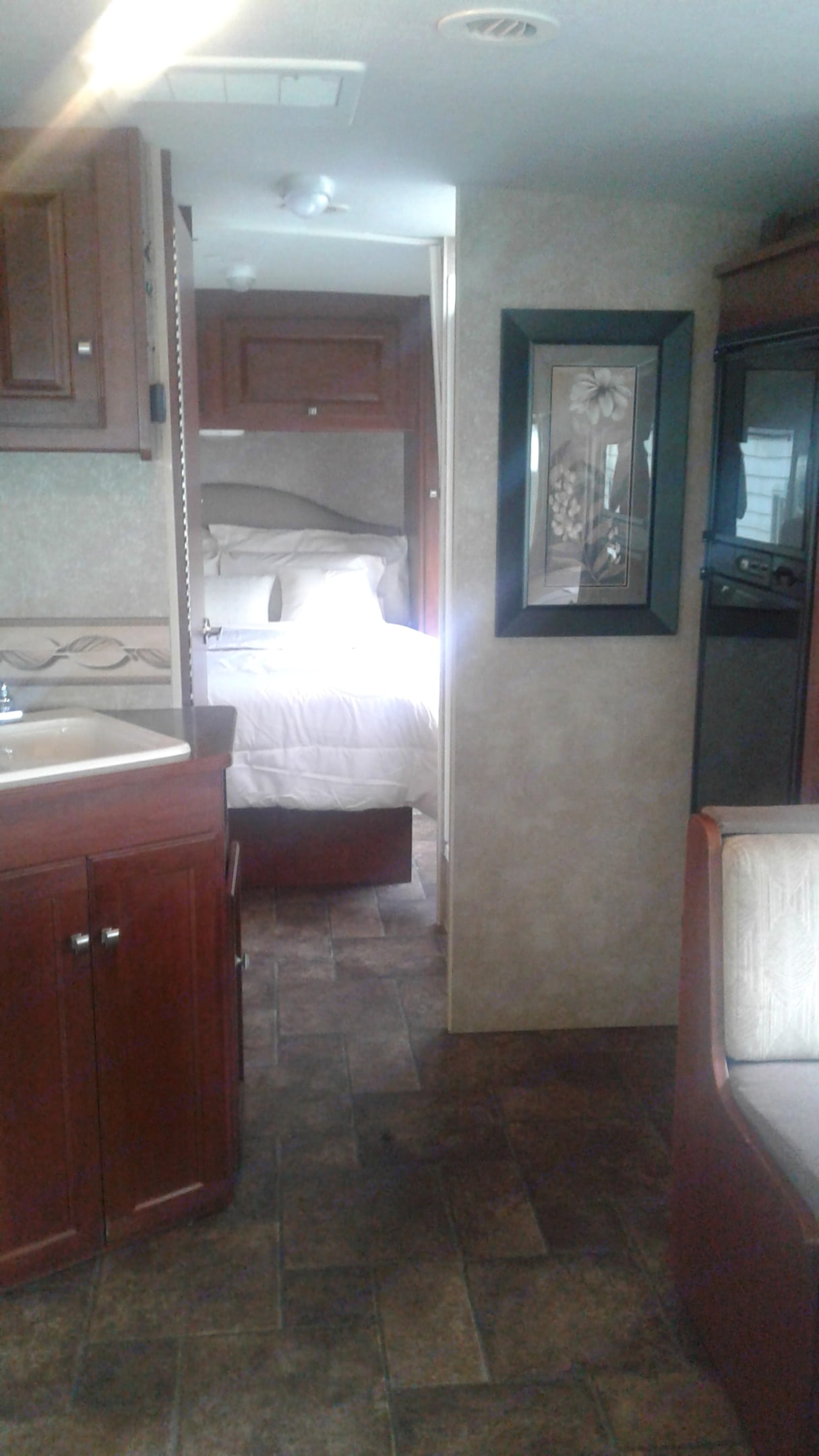Southern Comfort Queen side bed with fresh crisp hand pressed linen, close door become a master bedroom with bath. Picture come to view when slide is out.. Winnebago Vista 2013