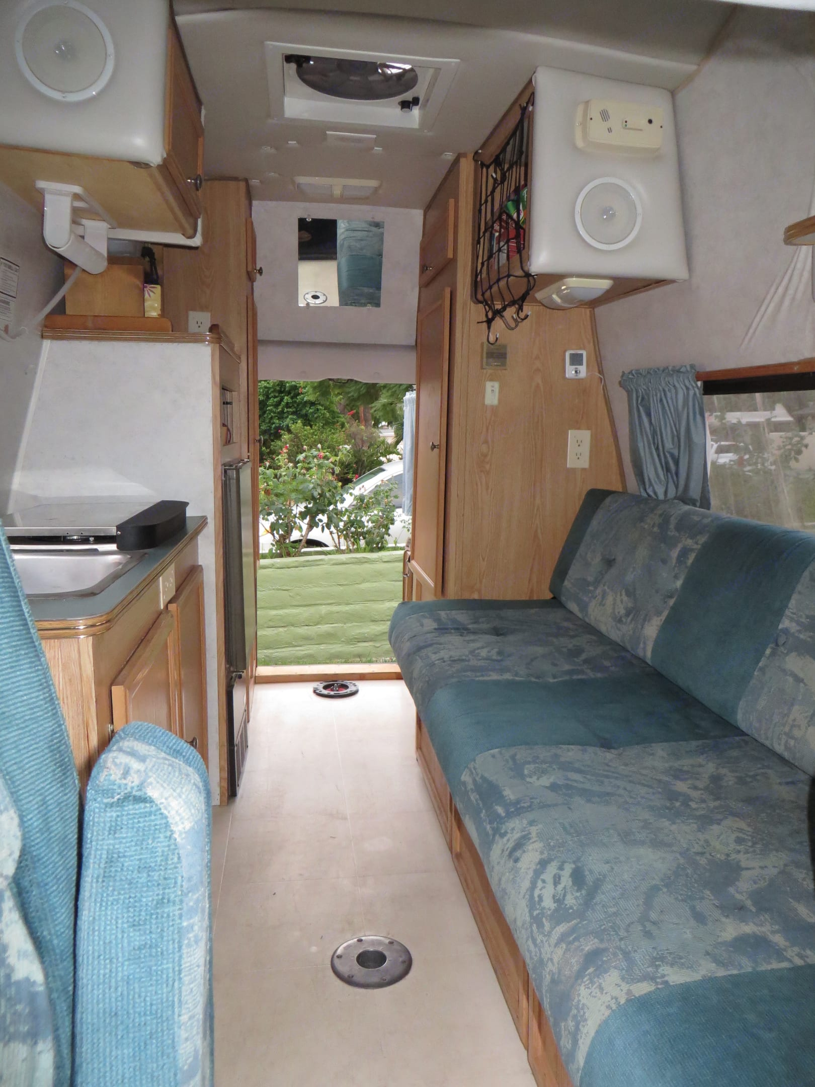 View of bench seating (2 seat belts), ample storage, refrigerator, sink and stove.. Phoenix (Shorty) Dodge 2000