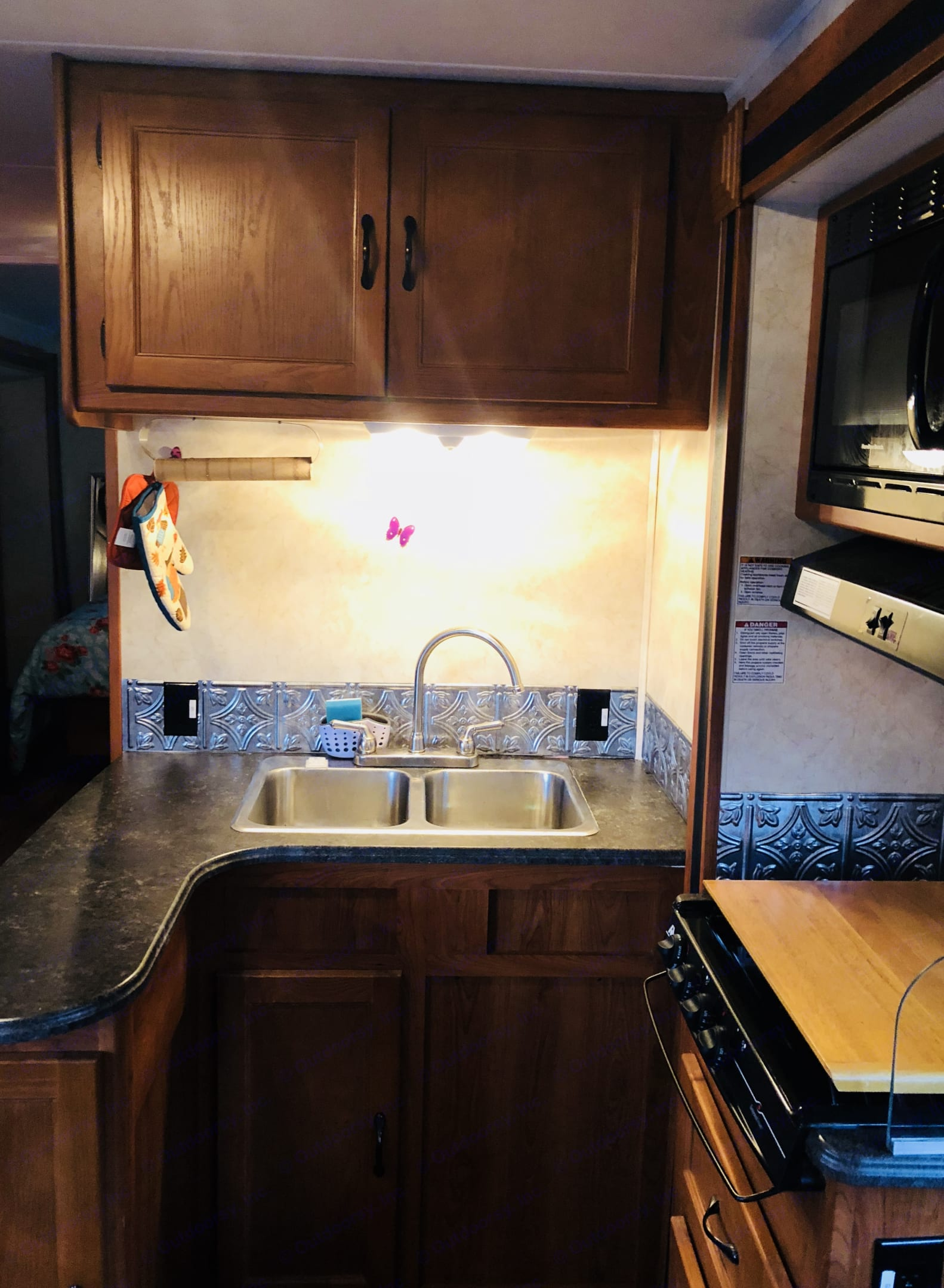 Kitchen with new backsplash and a full sink, stove top, and microwave. Also comes equipped with pots and pans and utensils. . Coachmen Freelander 2012